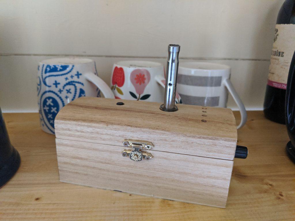 A VapOven DynaVap induction heater on a shelf with tea cups